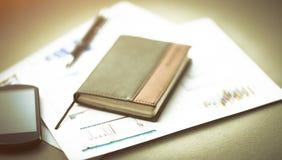 个人组织者和笔在书桌上图表背景  免版税图库摄影
