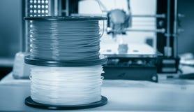 个人3d打印机和吸收或者pla细丝在他旁边盘绕 免版税库存图片