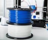 个人3d打印机和吸收或者pla细丝在他旁边盘绕 库存照片