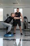 个人Bosu平衡球的教练员帮助的人 免版税库存照片