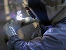 个体防护用品焊接管子的工作者人 免版税图库摄影