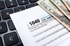 个体1040在膝上型计算机键盘的纳税申报形式 库存图片