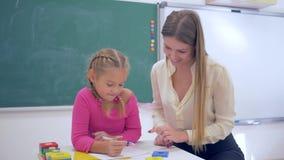 个别辅导,女性教育家帮助对学者女孩获取信息使用塑料图在桌上在黑板附近  影视素材