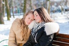 2个可爱的迷人的女孩坐一条长凳在他们中的一个在别的肩膀倾斜的冬天 图库摄影
