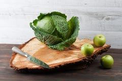 整个圆白菜和苹果在概略的木砧板 免版税库存图片