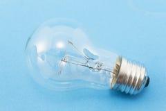 100个在蓝色背景的W电灯泡 免版税库存照片