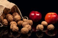 整个坚果和苹果在一张桌上在黑背景 图库摄影