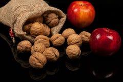 整个坚果和苹果在一张桌上在黑背景 库存图片