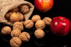 整个坚果和苹果在一张桌上在黑背景 免版税图库摄影