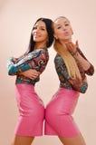 2个姐妹华美愉快一起微笑的图片白肤金发和深色的性感的少妇获得乐趣在皮革桃红色礼服 免版税库存图片
