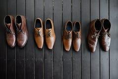 4个对men's变褐在黑木地板上的鞋子 免版税库存图片