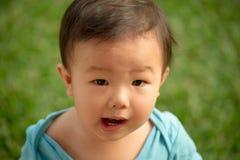 1个岁中国亚裔男孩佩带的连裤外衣在庭院里 库存照片