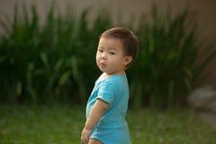 1个岁中国亚裔男孩佩带的连裤外衣在庭院里 免版税库存照片
