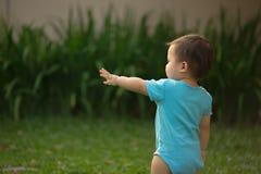 1个岁中国亚裔男孩佩带的连裤外衣在庭院里 库存图片