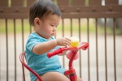 1个岁中国亚裔骑自行车的男孩佩带的连裤外衣 库存照片