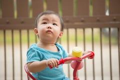1个岁中国亚裔骑自行车的男孩佩带的连裤外衣 免版税图库摄影