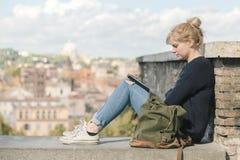 16 10 2015个年轻人读一本电子书的学生女孩在公园,罗马 免版税库存图片