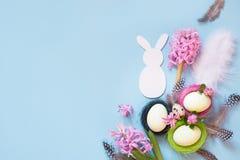 2个所有时段小鸡概念复活节彩蛋开花草被绘的被安置的年轻人 白色兔宝宝和被绘的鸡怂恿与在蓝色的花装饰 顶视图 平的位置 免版税库存图片
