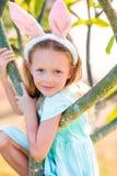 2个所有时段小鸡概念复活节彩蛋开花草被绘的被安置的年轻人 可爱的小女孩佩带的兔宝宝耳朵在春日 图库摄影