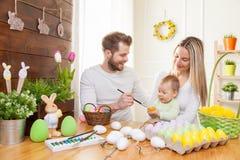 2个所有时段小鸡概念复活节彩蛋开花草被绘的被安置的年轻人 愉快的母亲和父亲与他们的孩子的家庭装饰为复活节假日做准备 免版税库存图片