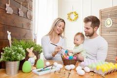 2个所有时段小鸡概念复活节彩蛋开花草被绘的被安置的年轻人 愉快的母亲和父亲与他们的孩子的家庭装饰为复活节假日做准备 免版税库存照片