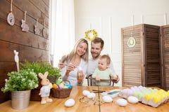 2个所有时段小鸡概念复活节彩蛋开花草被绘的被安置的年轻人 愉快的母亲和父亲与他们的孩子的家庭装饰为复活节假日做准备 库存照片