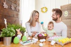 2个所有时段小鸡概念复活节彩蛋开花草被绘的被安置的年轻人 愉快的母亲和父亲与他们的孩子的家庭装饰为复活节假日做准备 图库摄影