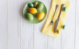 2个所有时段小鸡概念复活节彩蛋开花草被绘的被安置的年轻人 板材,叉子,在白色背景的鸡蛋 免版税库存图片