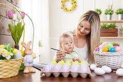 2个所有时段小鸡概念复活节彩蛋开花草被绘的被安置的年轻人 愉快的准备好母亲和她逗人喜爱的孩子复活节 图库摄影