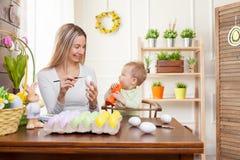 2个所有时段小鸡概念复活节彩蛋开花草被绘的被安置的年轻人 愉快的准备好母亲和她逗人喜爱的孩子复活节 免版税图库摄影