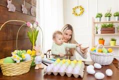 2个所有时段小鸡概念复活节彩蛋开花草被绘的被安置的年轻人 愉快的准备好母亲和她逗人喜爱的孩子复活节 库存图片