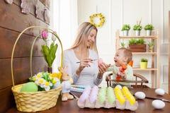 2个所有时段小鸡概念复活节彩蛋开花草被绘的被安置的年轻人 愉快的准备好母亲和她逗人喜爱的孩子复活节 库存照片