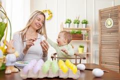 2个所有时段小鸡概念复活节彩蛋开花草被绘的被安置的年轻人 愉快的准备好母亲和她逗人喜爱的孩子复活节 免版税库存图片