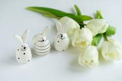 2个所有时段小鸡概念复活节彩蛋开花草被绘的被安置的年轻人 库存图片
