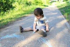 20个月与白垩的婴孩绘画在夏天 免版税库存图片