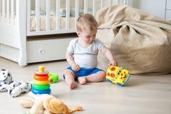 10个月使用与在地板上的五颜六色的玩具的小孩男孩在卧室 免版税库存照片