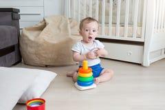 9个月使用在地板和聚集的玩具塔上的婴孩 库存照片