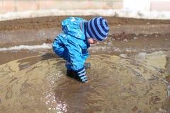 18个月使用在水坑的婴孩 免版税库存照片