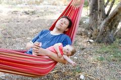6个月和她父亲睡觉的逗人喜爱的可爱的女婴平安在吊床在室外庭院里 图库摄影