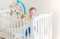 10个月哭泣和举行对小儿床的边的男婴 免版税库存照片