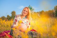 9个月坐在黄色草和微笑的孕妇 等待的婴孩 怀孕概念 免版税库存照片