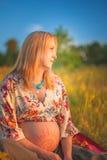 9个月坐在黄色草和微笑的孕妇 等待的婴孩 怀孕概念 免版税库存图片