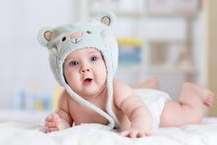 5个月女婴在躺下在毯子的滑稽的帽子weared 免版税库存图片