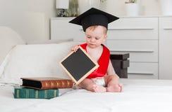 10个月拿着黑粉笔板的毕业帽子和红色丝带的男婴 免版税库存图片