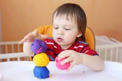 18个月有彩色塑泥的婴孩在家 免版税图库摄影