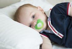 10个月特写镜头画象说谎在枕头和拿着soother的男婴 免版税图库摄影