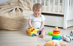 10个月男婴坐与五颜六色的玩具汽车的地板 免版税库存照片