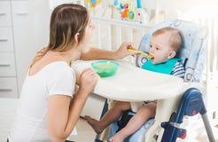 10个月画象坐在高脚椅子和eatting的粥的男婴从匙子 免版税库存图片