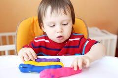 18个月的可爱的婴孩年龄与彩色塑泥的在家 免版税库存照片