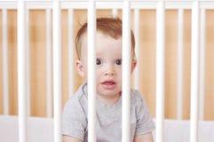10个月的可爱的婴孩年龄在白色床上 免版税库存图片
